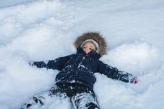 Menina que encontra-se em uma neve profunda imagens de stock