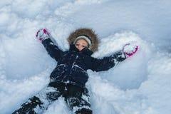Menina que encontra-se em uma neve profunda imagens de stock royalty free