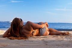 Menina que encontra-se em uma praia Imagem de Stock