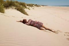 Menina que encontra-se em uma praia arenosa Fotografia de Stock Royalty Free