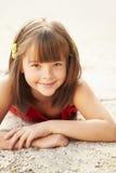 Menina que encontra-se na areia Foto de Stock Royalty Free