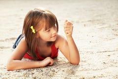 Menina que encontra-se na areia Fotografia de Stock Royalty Free