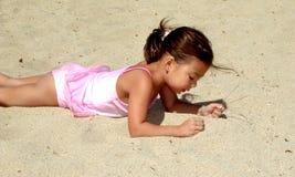 Menina que encontra-se na areia Imagens de Stock Royalty Free