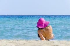 Menina que encontra-se na areia da praia fotografia de stock