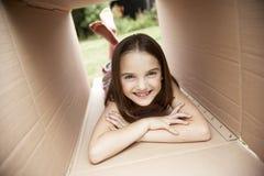 Menina que encontra-se na caixa de cartão fotografia de stock