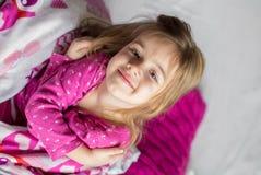 Menina que encontra-se na cama Fotografia de Stock
