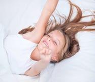 Menina que encontra-se na cama branca Imagens de Stock Royalty Free