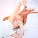 Menina que encontra-se na cama branca Fotografia de Stock