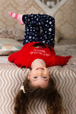 Menina que encontra-se na cama de cabeça para baixo Imagens de Stock