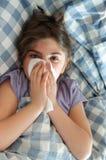 Menina que encontra-se na cama que espirra seu nariz Fotografia de Stock Royalty Free