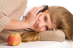 Menina que encontra-se na cama usando o telefone de pilha Fotografia de Stock