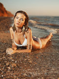 Menina que encontra-se na costa de mar Imagens de Stock Royalty Free