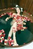 Menina que encontra-se na cuba de água - vertical Foto de Stock Royalty Free