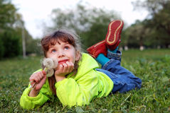 Menina que encontra-se na grama Foto de Stock Royalty Free