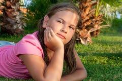Menina que encontra-se na grama. Fotos de Stock
