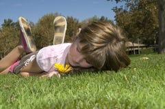 Menina que encontra-se na grama Imagens de Stock Royalty Free