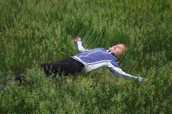 A menina que encontra-se na grama Imagens de Stock Royalty Free