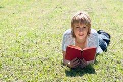 Menina que encontra-se na grama e no livro de leitura Foto de Stock Royalty Free