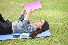 Menina que encontra-se na grama e no livro lido Fotos de Stock