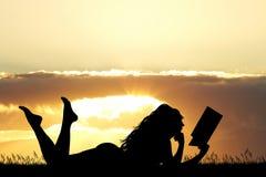 A menina que encontra-se na grama lê um livro no por do sol Imagem de Stock