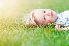Menina que encontra-se na grama na mola Imagens de Stock Royalty Free