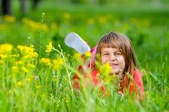 Menina que encontra-se na grama na mola Foto de Stock Royalty Free