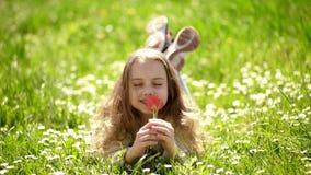 Menina que encontra-se na grama, natureza em fundo, defocused A crian?a aprecia o dia ensolarado da mola ao encontrar-se no prado vídeos de arquivo