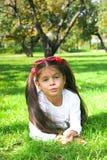 Menina que encontra-se na grama no parque Imagens de Stock Royalty Free