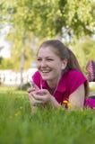 Menina que encontra-se na grama verde Imagens de Stock