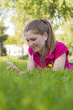 Menina que encontra-se na grama verde Foto de Stock