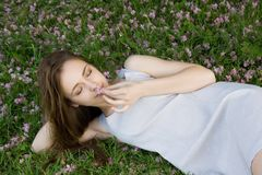 Menina que encontra-se na grama verde com flores Foto de Stock Royalty Free