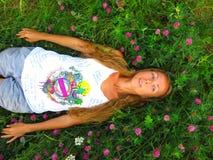 Menina que encontra-se na grama verde no verão Prado com trevo lon Foto de Stock Royalty Free