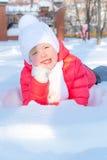 Menina que encontra-se na neve no parque Imagem de Stock Royalty Free