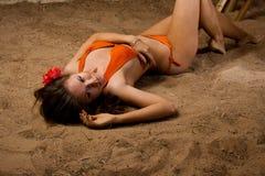 Menina que encontra-se na praia Fotos de Stock Royalty Free