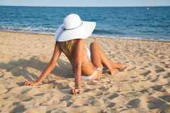 Menina que encontra-se na praia Foto de Stock
