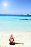 Menina que encontra-se na praia branca da areia Fotos de Stock