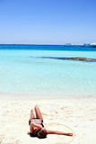 Menina que encontra-se na praia branca da areia Fotografia de Stock Royalty Free