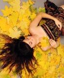 Menina que encontra-se nas folhas. Imagens de Stock
