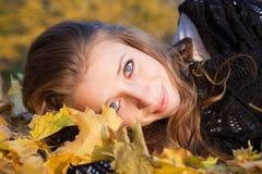 Menina que encontra-se nas folhas Fotos de Stock Royalty Free