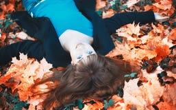 Menina que encontra-se nas folhas de outono Fotografia de Stock Royalty Free