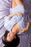 Menina que encontra-se nela para trás em uma cama Foto de Stock