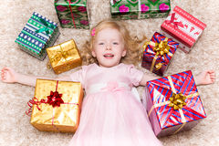 Menina que encontra-se no assoalho cercado por presentes do Natal Imagem de Stock Royalty Free