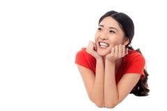 Menina que encontra-se no assoalho do estúdio e que pensa algo Foto de Stock Royalty Free