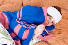 Menina que encontra-se no doente do sofá Fotografia de Stock