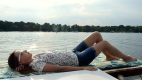 A menina que encontra-se no iate do barco de vela aprecia o mar em um navio grande ao navegar no mar vídeos de arquivo