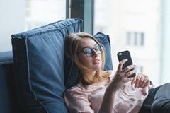 Menina que encontra-se no sofá e que usa um smartphone A menina está descansando no sofá com um smartphone em suas mãos imagem de stock