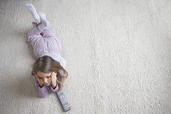 Menina que encontra-se no tapete com controlo a distância Imagem de Stock