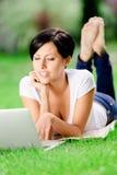 Menina que encontra-se nos trabalhos de grama verde no computador Imagem de Stock Royalty Free