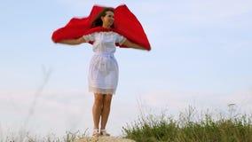 Menina que engana ao redor estar em um campo em um casaco vermelho, jogando o super-herói a mulher alegre joga em um casaco verme vídeos de arquivo