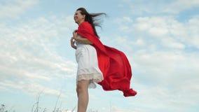 Menina que engana ao redor estar no campo no casaco vermelho, jogando o super-herói A mulher alegre joga no casaco vermelho com e vídeos de arquivo